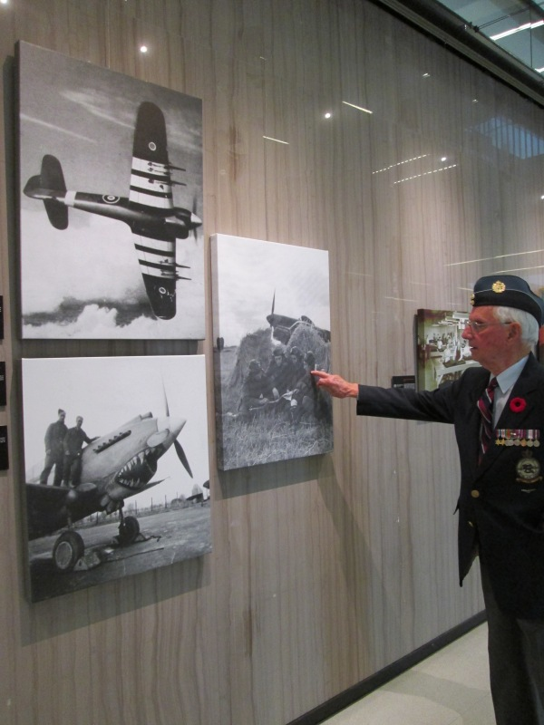 John Thompson pointing to an image of himself on display for the Service and Sacrifice exhibition at Vaughan City Hall.