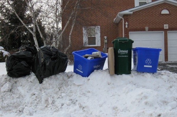 The INCORRECT way to place your waste and recycling. Waste collectors will not collect waste materials that are placed behind or on top of snowbanks.